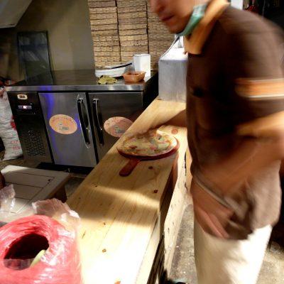 Proses pembuatan pizza tungku - memotong pizza