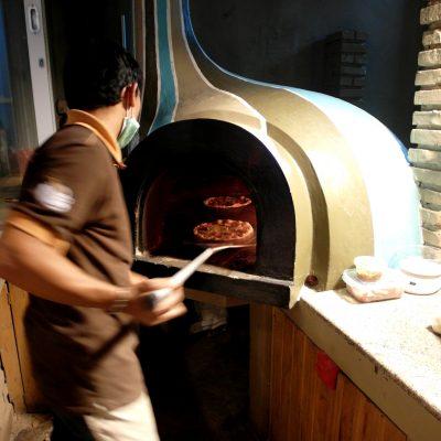 Proses pembuatan pizza tungku - memasukkan pizza ke dalam tungku