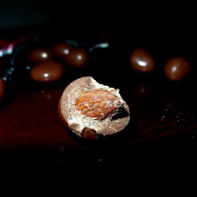 Butiran coklat butir Van Houten Assortment isi kacang almond udah digigit setengahnya.