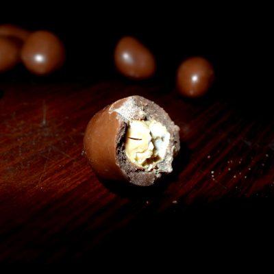 Butiran coklat butir Van Houten Assortment isi kacang mete udah digigit setengahnya.